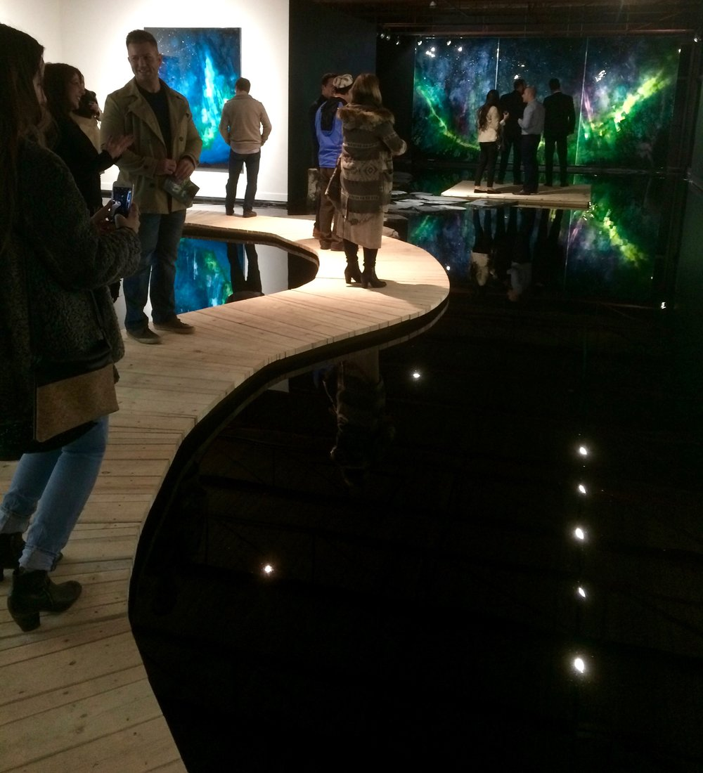 Visitors to the gallery must walk along a wooden walkway that leads to a dock