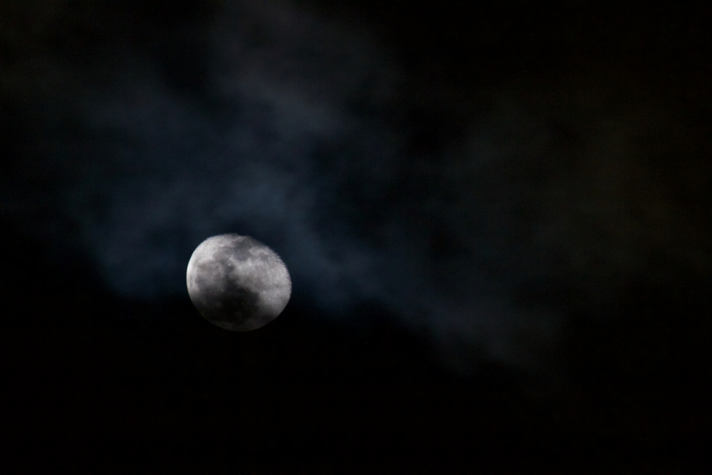 The waning gibbous moon peeks from behind the clouds after a rainstorm. (John McPhee)