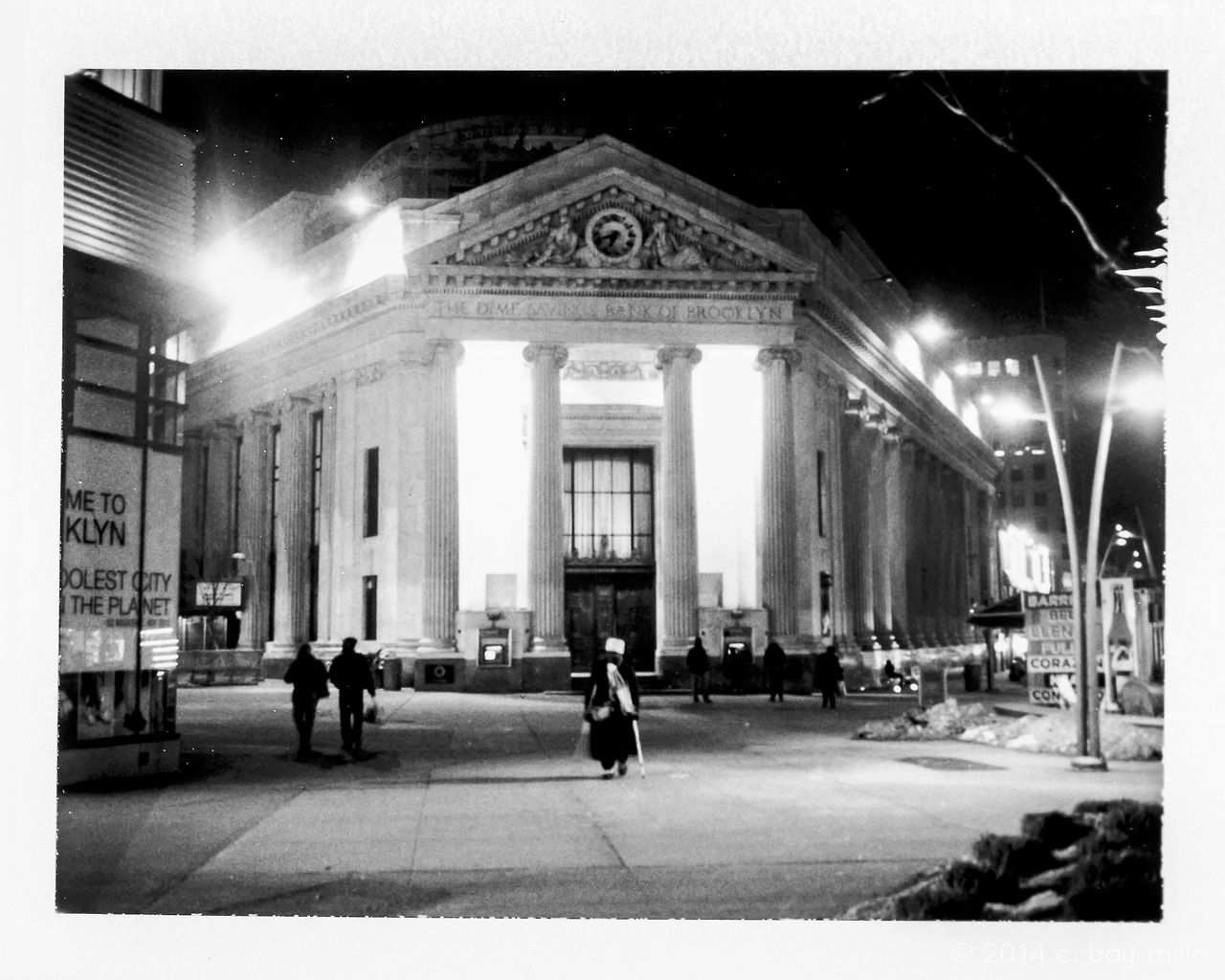 —-  nighttime develops a cool ice grip nearing 8°F, and a single figure on crutches shuffles across the square.  each person in the nearby shops and down the frigid alleyways clutch the collar of their coats, in an attempt to capture as much body-warmth as possible.  the dime savings bank of brooklyn looms o'er with a historical stoutness, and the developing windstorm skirts the edges.  —-