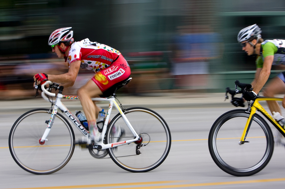Brad Huff (left) of the Jelly Belly Cycling Team leads a breakaway group during the Queen City Criterium on E. Commercial Street.