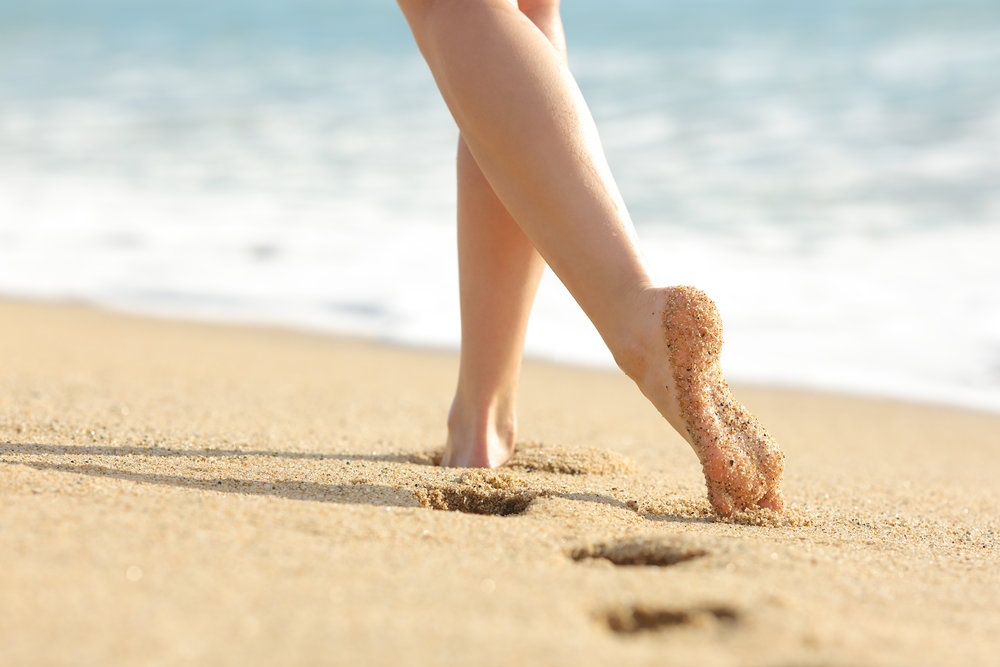 Woman legs and feet walking on the sand of the beach.jpg