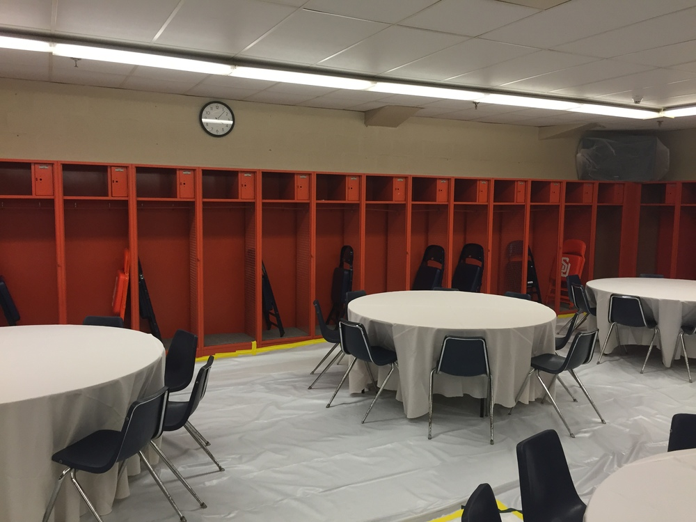 Football and basketball locker room setup with tables for craft services for the Monster Jam crew.