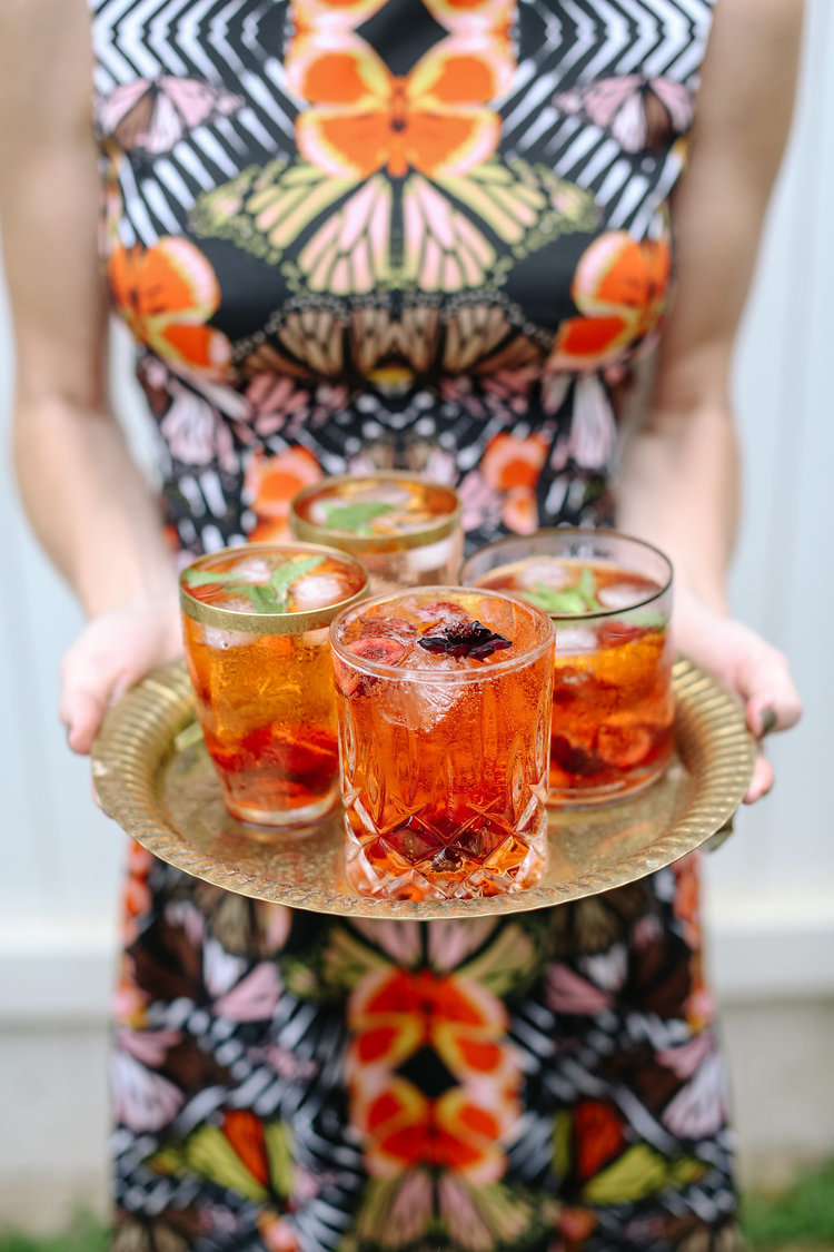 Aperol Spritz served in Double Old Fashioned glasses and garnished with chocolate cosmos and mint. See recipe below.