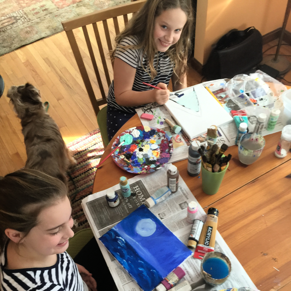 Dining room table paint studio. Both girls are painting from their imaginations.
