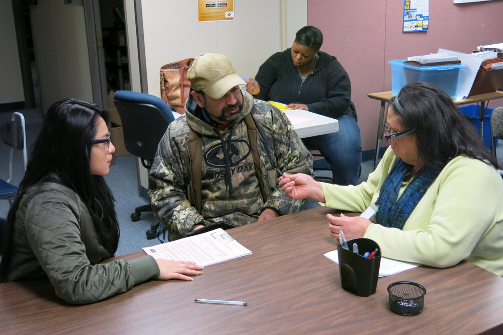 Yohana Gomez, left, and her stepdad, Rogelio Romo, fill out forms in Barb Wunsch's office. Gomez started the year in Hickman Mills, moved to Kansas City, Kansas, to live with a relative, before returning to the district. CREDIT ELLE MOXLEY