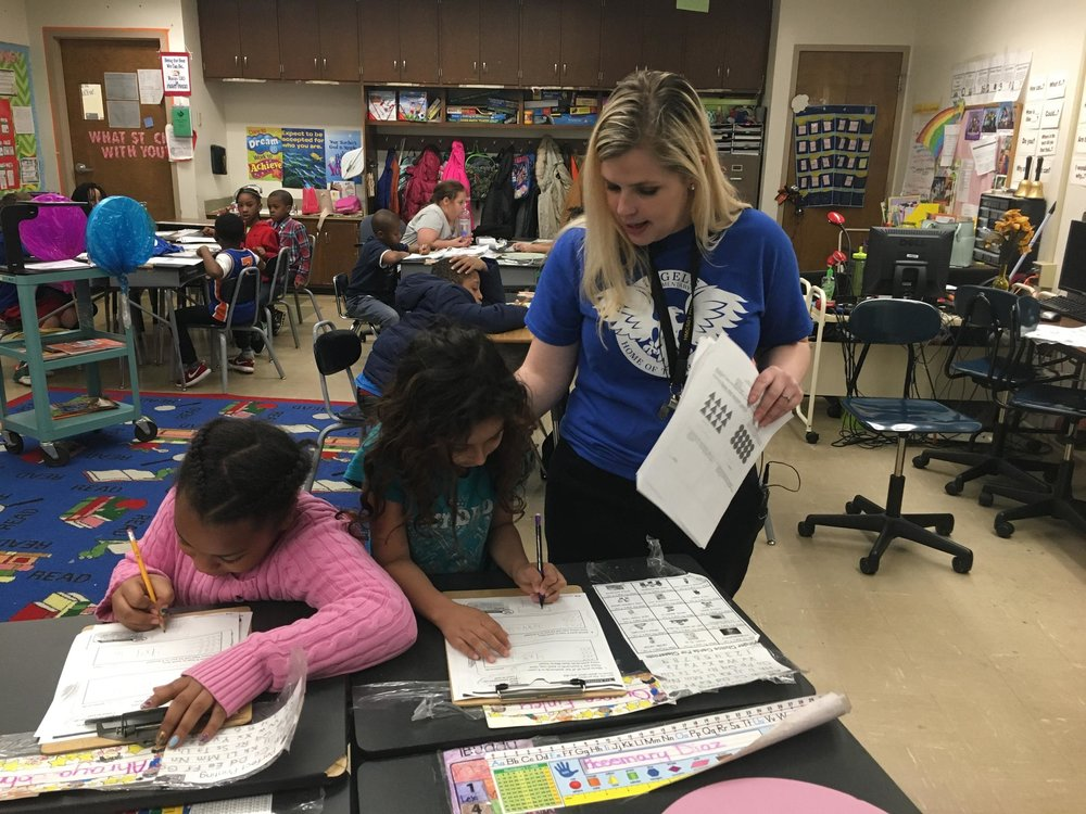 Second grade teacher Aubrey Paine helps students Ahraya and Rosemary with an assignment. ELLE MOXLEY / KCUR 89.3