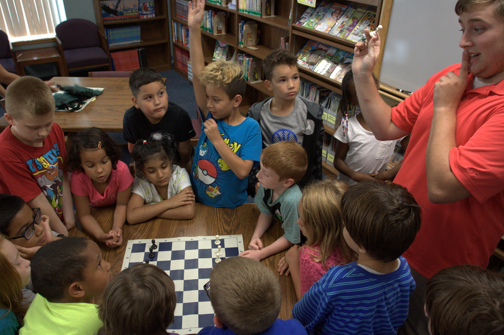 LINC Chess Coach Trenton teaches Chouteau Elementary students on how the pawn moves.