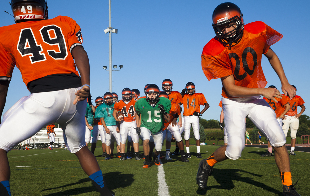 Seniors Zach Emswiler, middle, runs towards Stephan Day, left, and Donny Crabill, right, during Central York High School football practice, Wednesday, Aug. 14. 2013. DAILY RECORD / SUNDAY NEWS - SONYA PACLOB