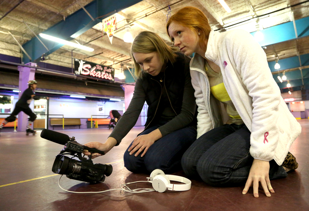 Kiah and Haley shoot low to the ground as roller derby team practice around them. Photo by Sonya Paclob