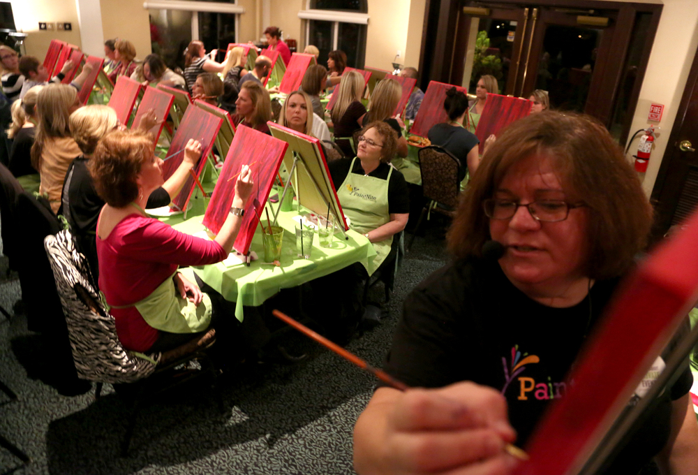 "isa Middendorf, Paint Nite instructor guides her participants in painting the ""Decorative Wine"" on canvas at Bogey Macaws. The event encourages non painters to come together with friends and have a drink, Middendorf said. She holds sessions at the restaurant every Monday that can host at about 40 participants in a private room.  Photo by Sonya Paclob"