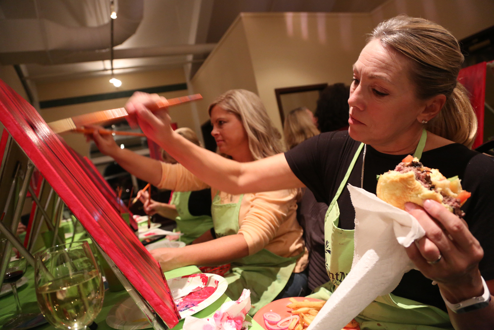 "Naomi Munkittrick from Dillsburg paints on her canvas with a brush and holds her burger in the other hand during Paint Nite at Bogey Macaws American Grille in York Township. Munkittrick admitted she was starving and said, ""When you are a mom, you learn to multitask.""  Photo by Sonya Paclob"