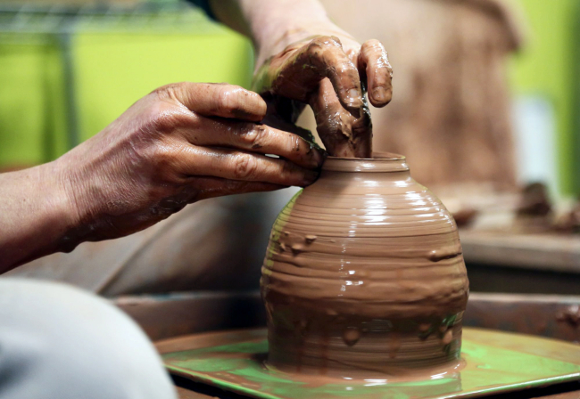 Kirsten Firlik, co-owner of Clay Path Studio, uses her fingers to guide the clay as it spins on a potter's wheel in York. The studio holds classes for beginners, advance and children. Photo by Sonya Paclob