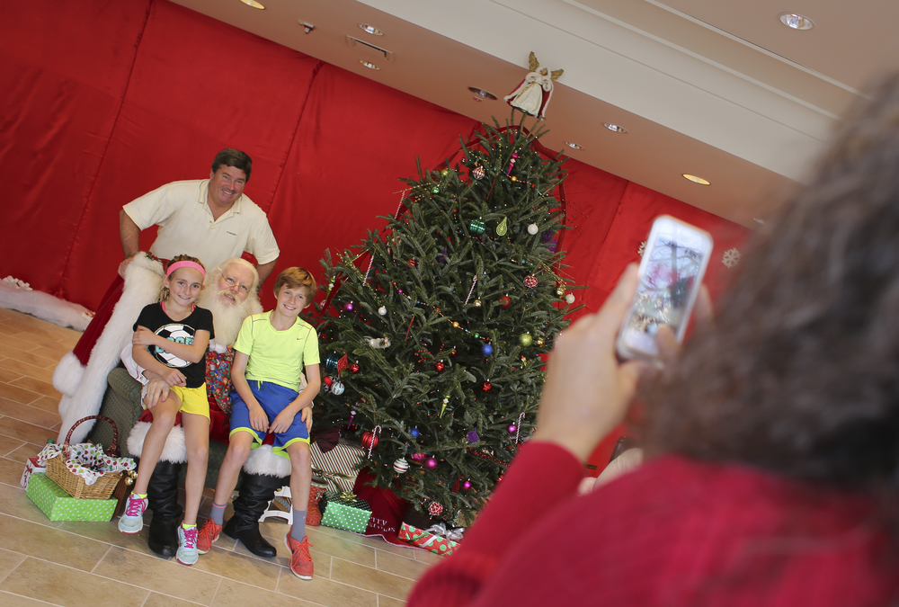 "Stuart Brown, Arlington, Va., smiles with his children from left, Kendall Brown, 10, and Peter Brown, 12, with Paul Sheehan as Santa Claus who looks at picture taker Deena Walls, worker for New Town Williamsburg, Friday, Nov. 27, 2015. I'm normally the photographer in the family, Brown said, I'm glad I can be in the picture this time."" Meeting with Santa and picture taking are free, said Paul. (Sonya Paclob / Special to the Daily Press)"