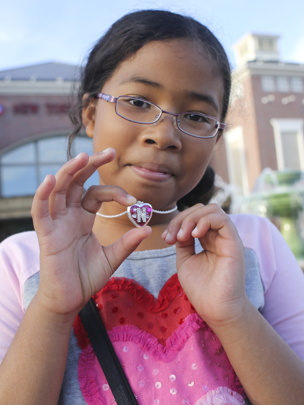 "Nina Gokita, 10, shows off her Black Friday purchase, a heart locket with the letter N at Justice in New Town Williamsburg, Friday, Nov. 27, 2015. According to her mother Tonya Gokita, Williamsburg, Nina bought the locket with her birthday money. ""I bought this for 40% off and I'm happy, Nina said. (Sonya Paclob / Special to the Daily Press)"