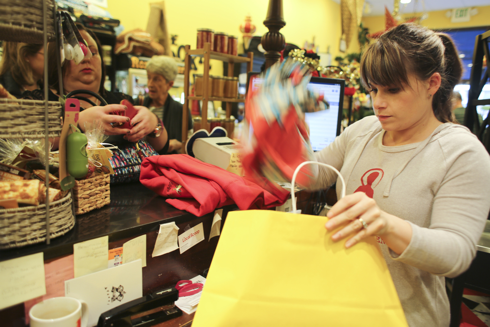Owner Amanda Wilbourne of Nautical Dog places dog related items in a bag for her loyal customer Amanda Stendardo, Woodbridge, Va., after purchases at New Town Williamsburg, Friday, Nov. 27, 2015. Wilbourne was offering her customers Nautical Dog cash for every $50 spent towards $10 off purchases in January, she said. She will also offer the deal tomorrow on Small Business Saturday. (Sonya Paclob / Special to the Daily Press)