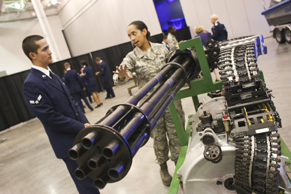 Senior Airman Chaleah Phillips talks to Airman First Class Gabriel Fox on the gun that goes into a F-15 at L  angley Air Force Base 100th Anniversary Gala, Hampton, Saturday, Sept. 17, 2016.