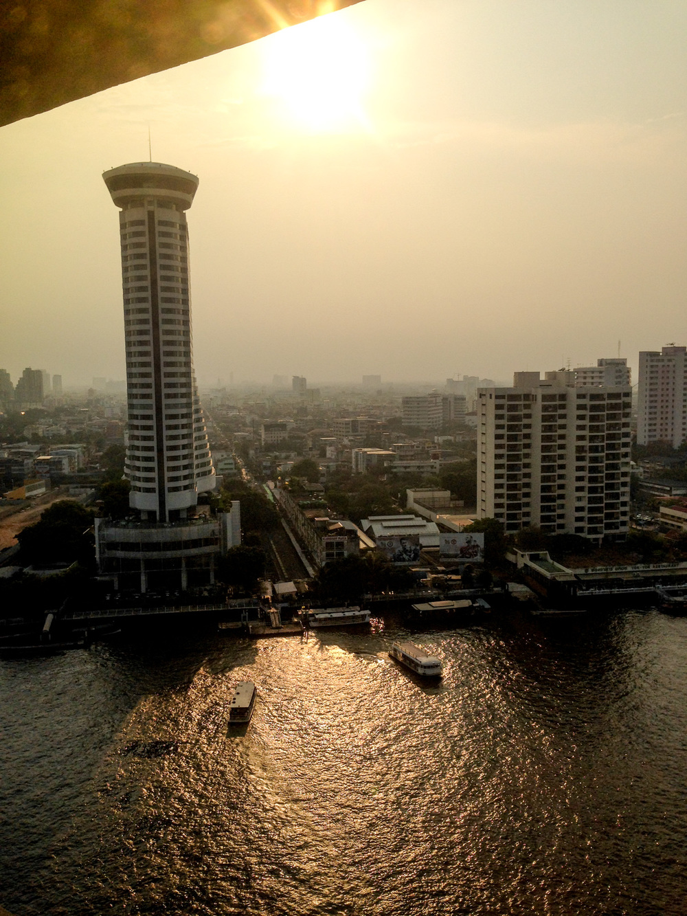 Sunset over the Chao Phraya river with the  Hilton Millennium  tower in the background.