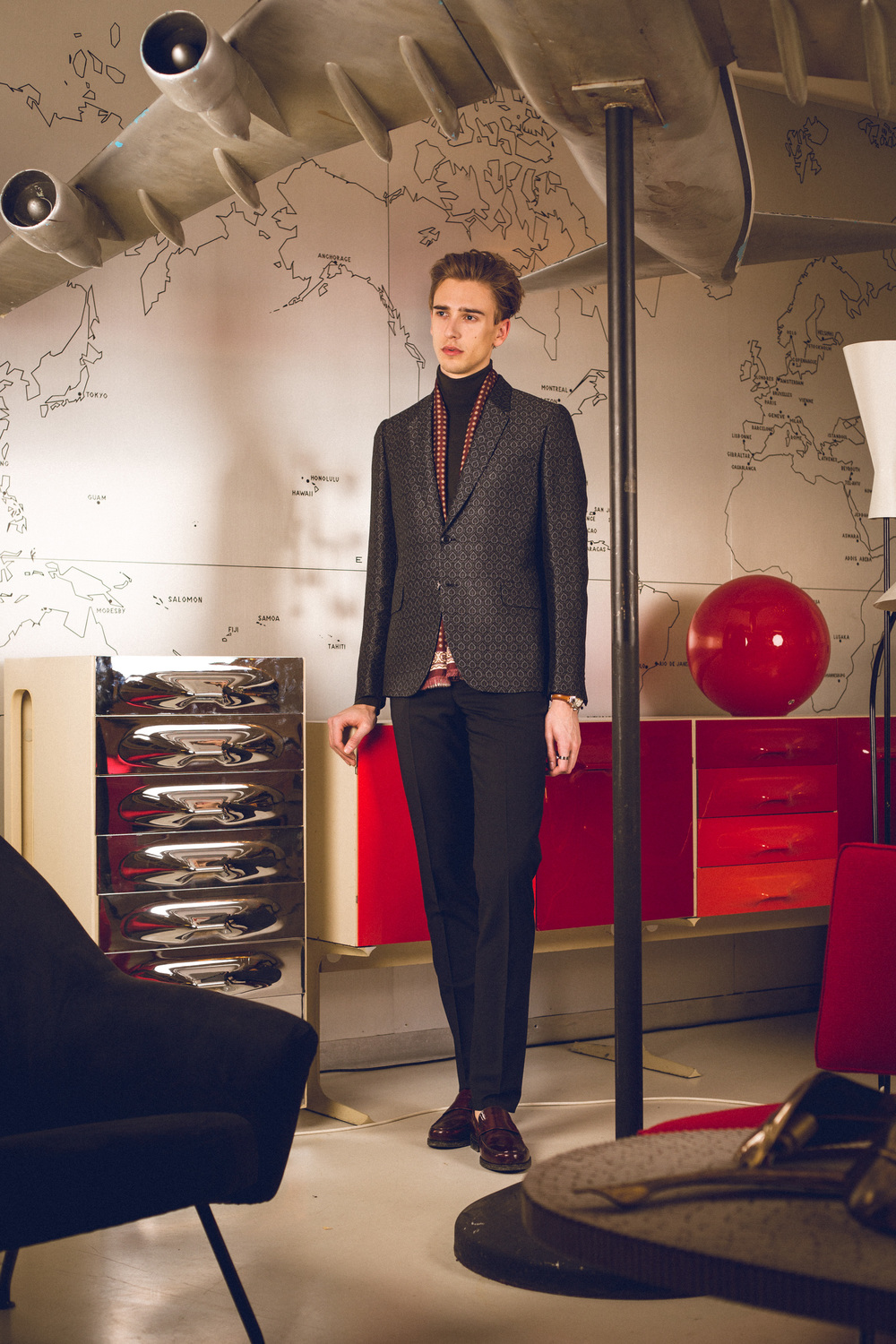 Oliver is wearing a Paul Smith suit and scarf, Fidelio roll neck sweater and Pedro loafers.