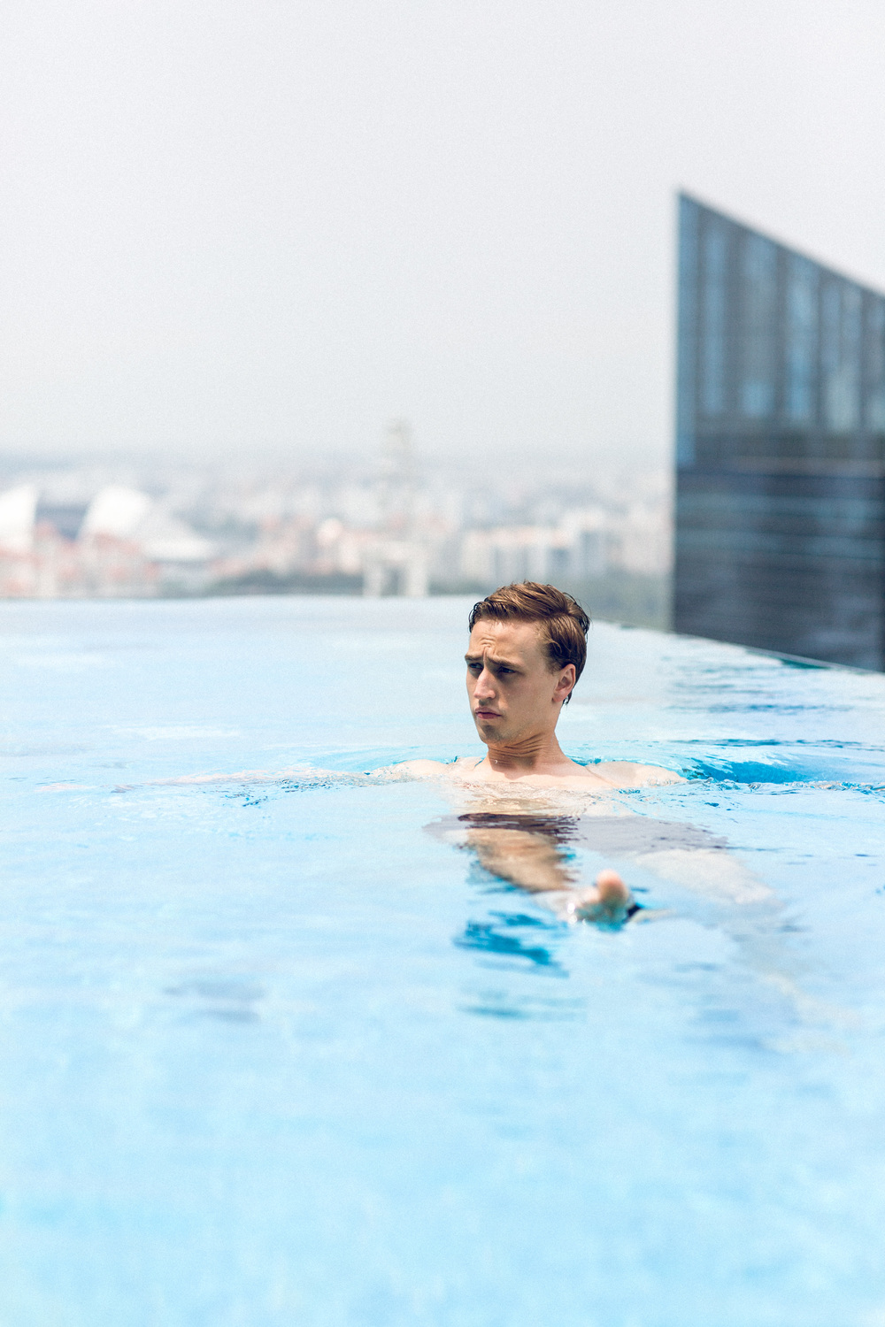 Moritz swimming in the infinity pool on the 35th floor overlooking Marina Bay.