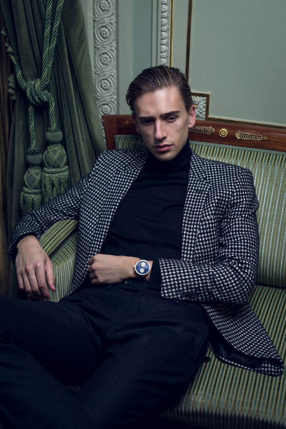 Oliver is wearing a Fidelio roll neck sweater and BOSS blazer and trousers.