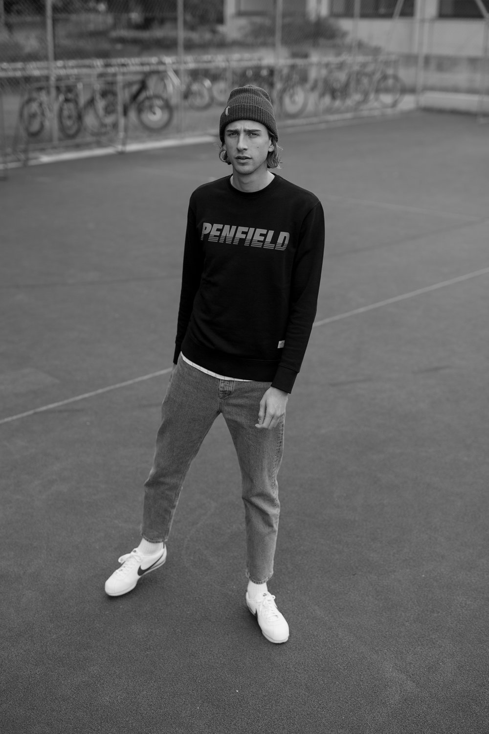 Oliver is wearing a Penfield sweatshirt, a pair of Topman jeans and Nike 'Cortez' sneakers.