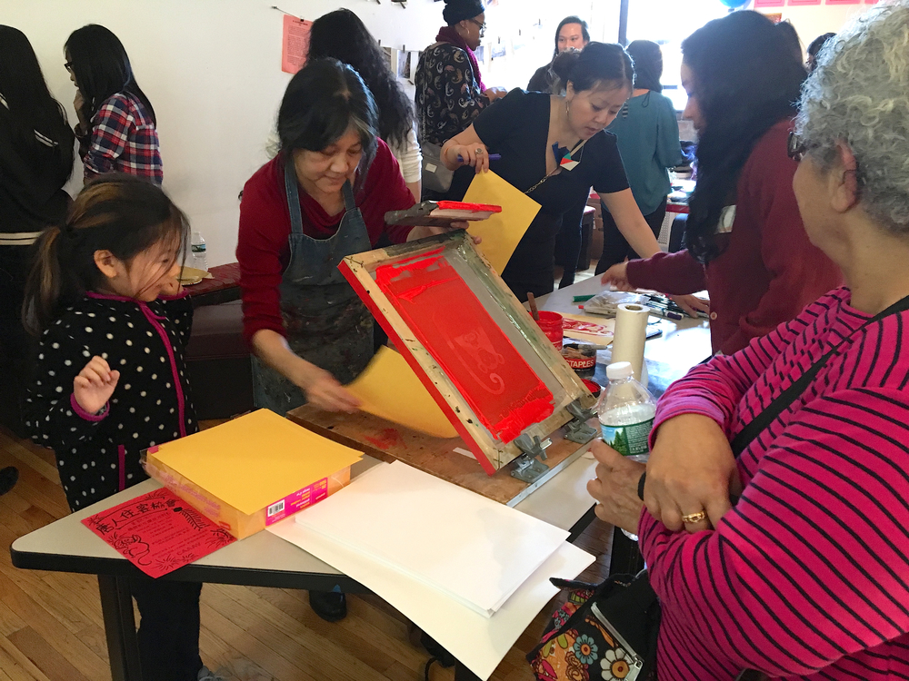 Chinatown Art Brigade's silkscreening station at CTU's Lunar New Year party. Tenants, youth, and volunteers took turns at the silkscreen station, designed and produced by Tomie Arai.
