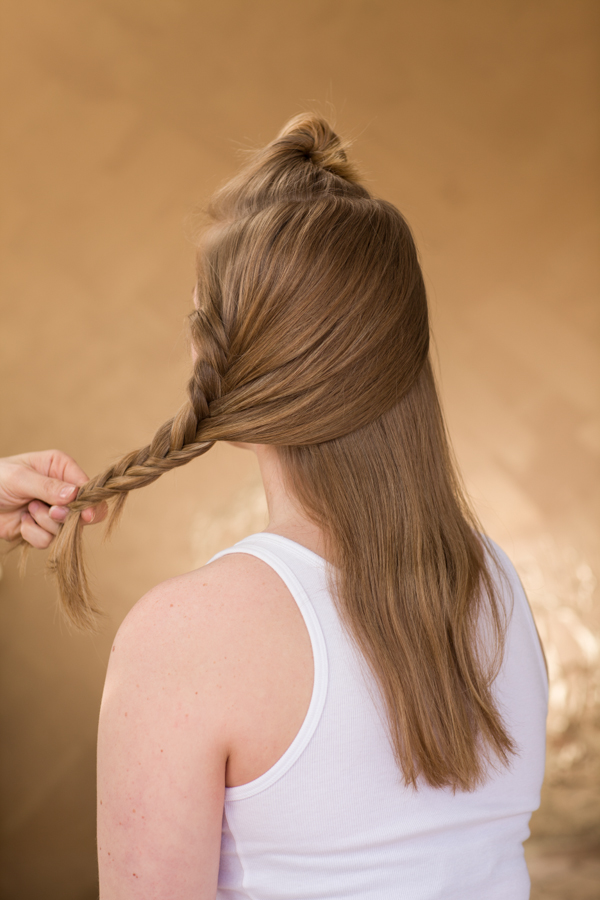 Create a horseshoe section at the top of the head and pin out of the way.  Starting on the right side of the head, grab a small section at the top front part the section to create a fishtail braid.   As you braid, add small sections wrapping around the head from the back side of the braid only.  Be sure to be directing your braid to the front of the shoulder as you are going.