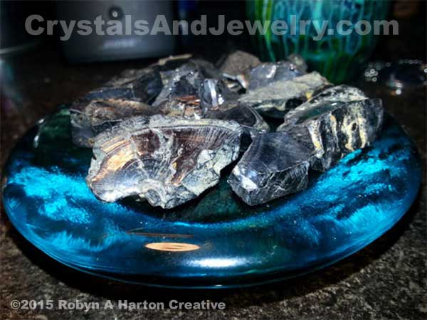 This shungite sitting on a blue glass plate  is so shiny it is picking up reflections from nearby objects.