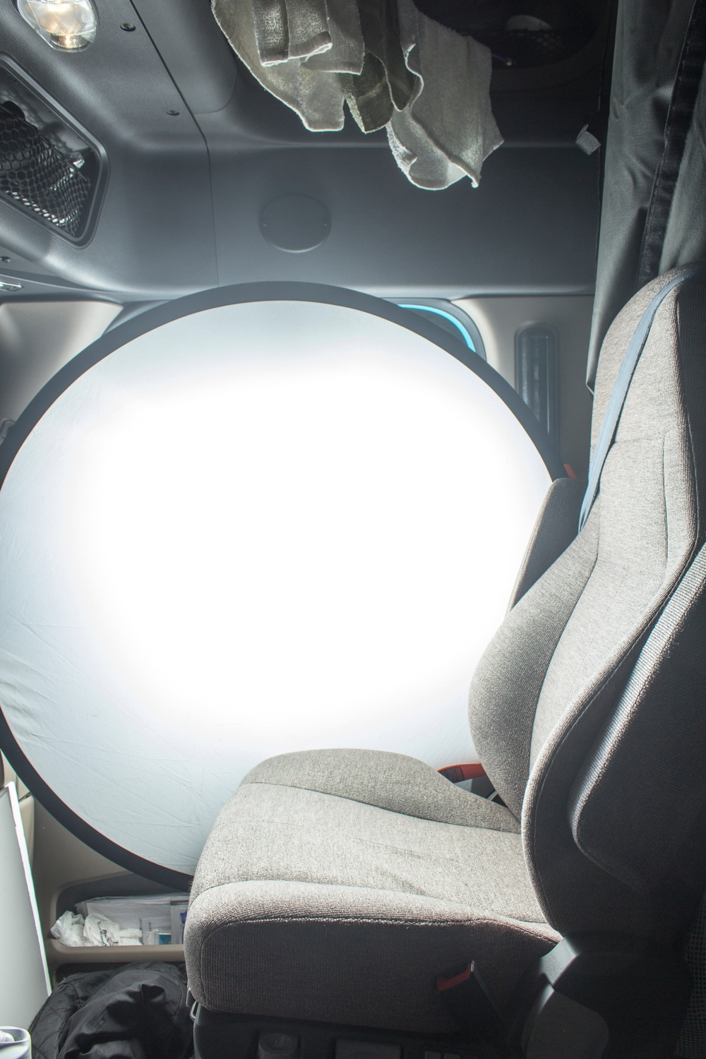 I picked up this folding 5-in-1 reflector/diffuser on sale for $44 last summer. I wedge it between the seat and door. The light from the flash bounces around between it and the foam core board. As you can see, it creates a giant soft back light using nearly no space in the truck. If I had the room to setup reflectors around the food then this one light would be enough. But since my space is so small I need to add another light.