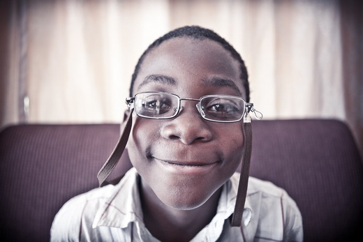 Malawian boy smiling after receiving new glasses