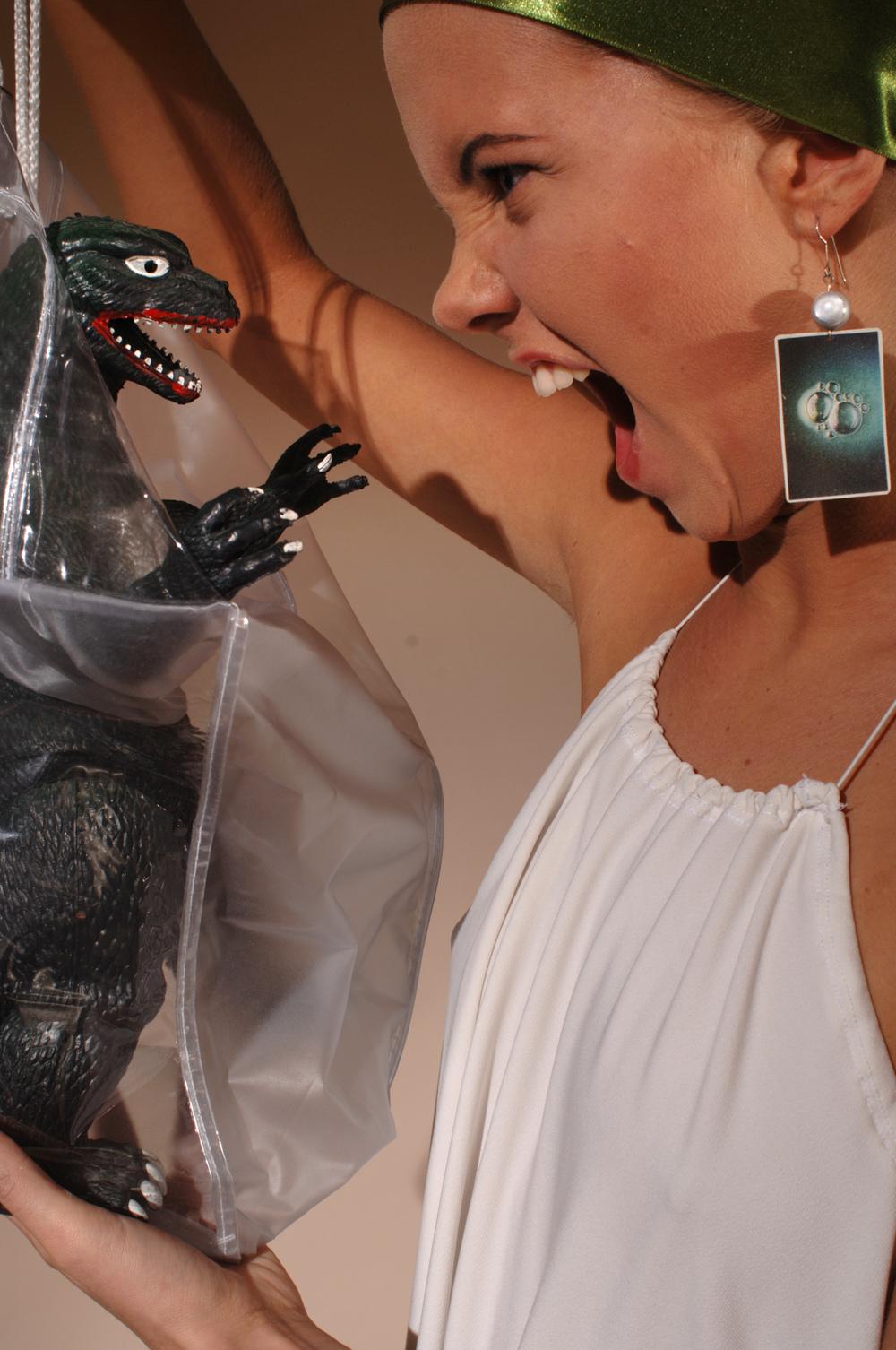 Girl screaming at a dinosaur in a bag