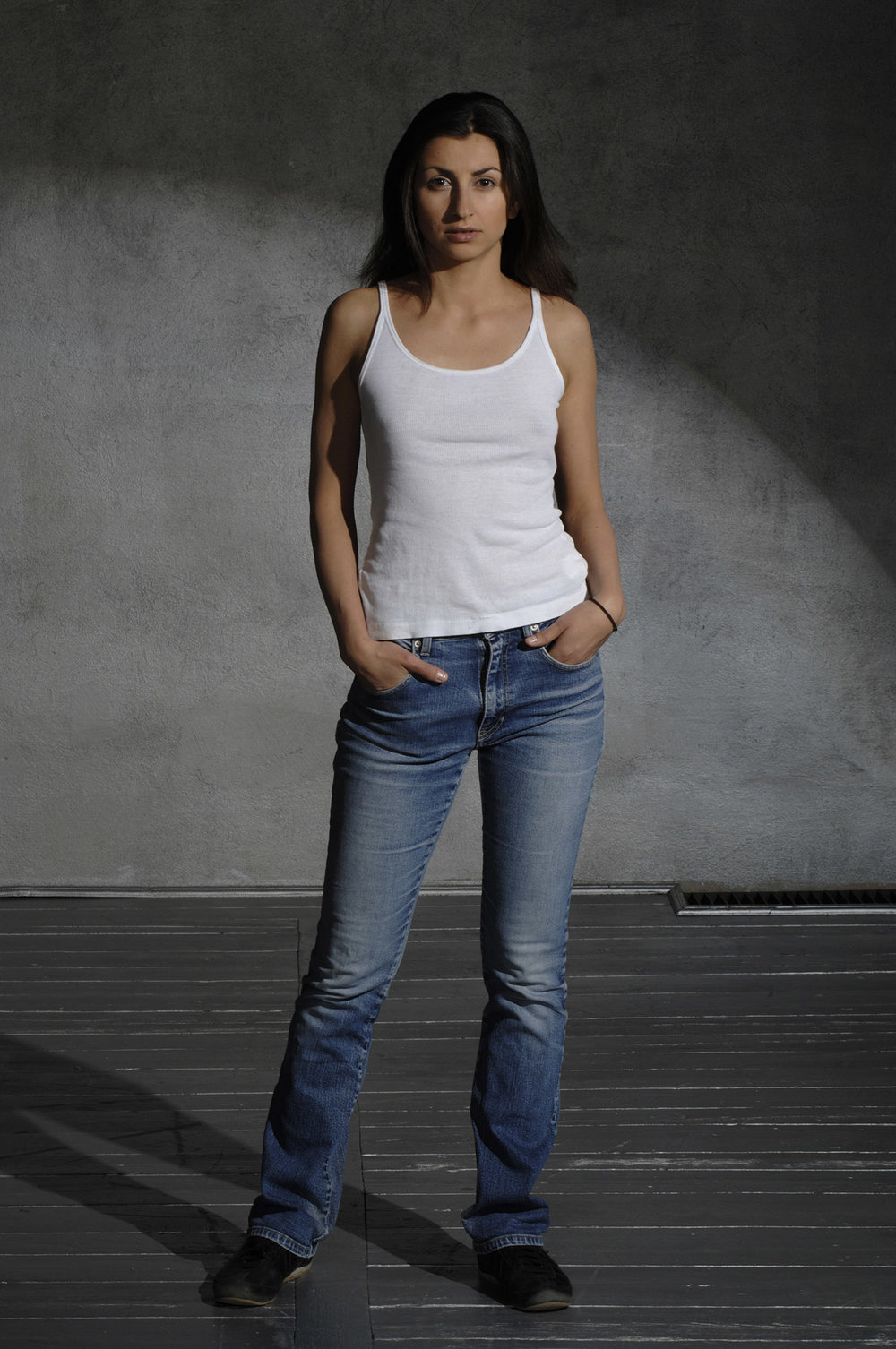 Dark haired girl in a white t-shirt  and jeans
