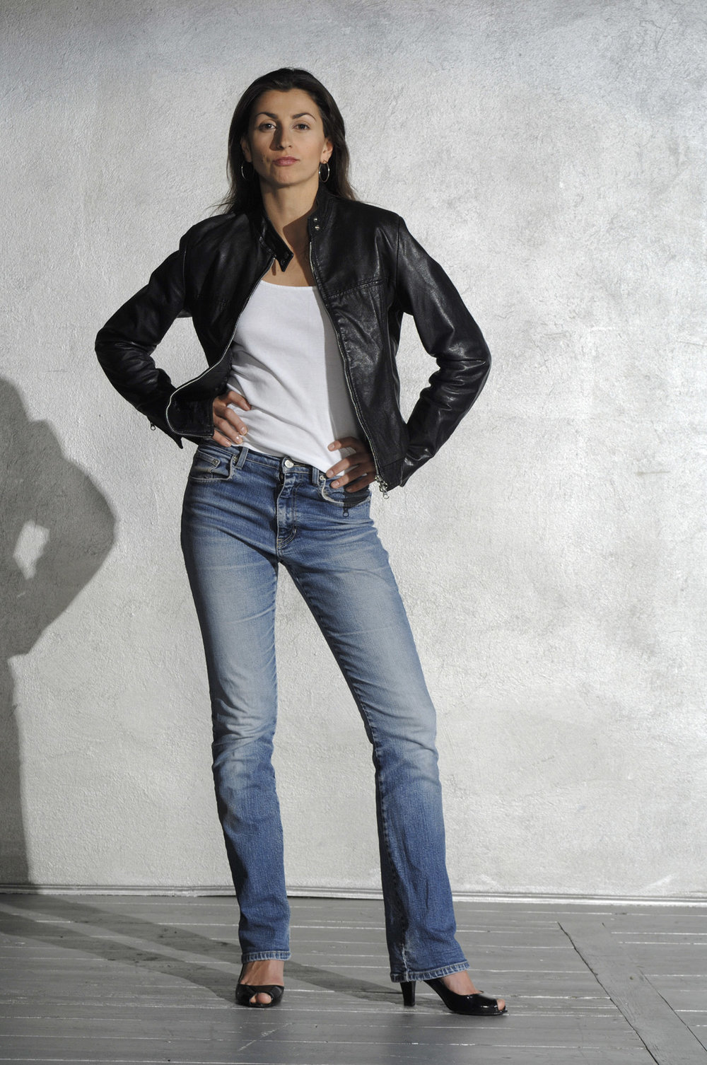 Dominant girl in a black leather jacket  and blue jeans