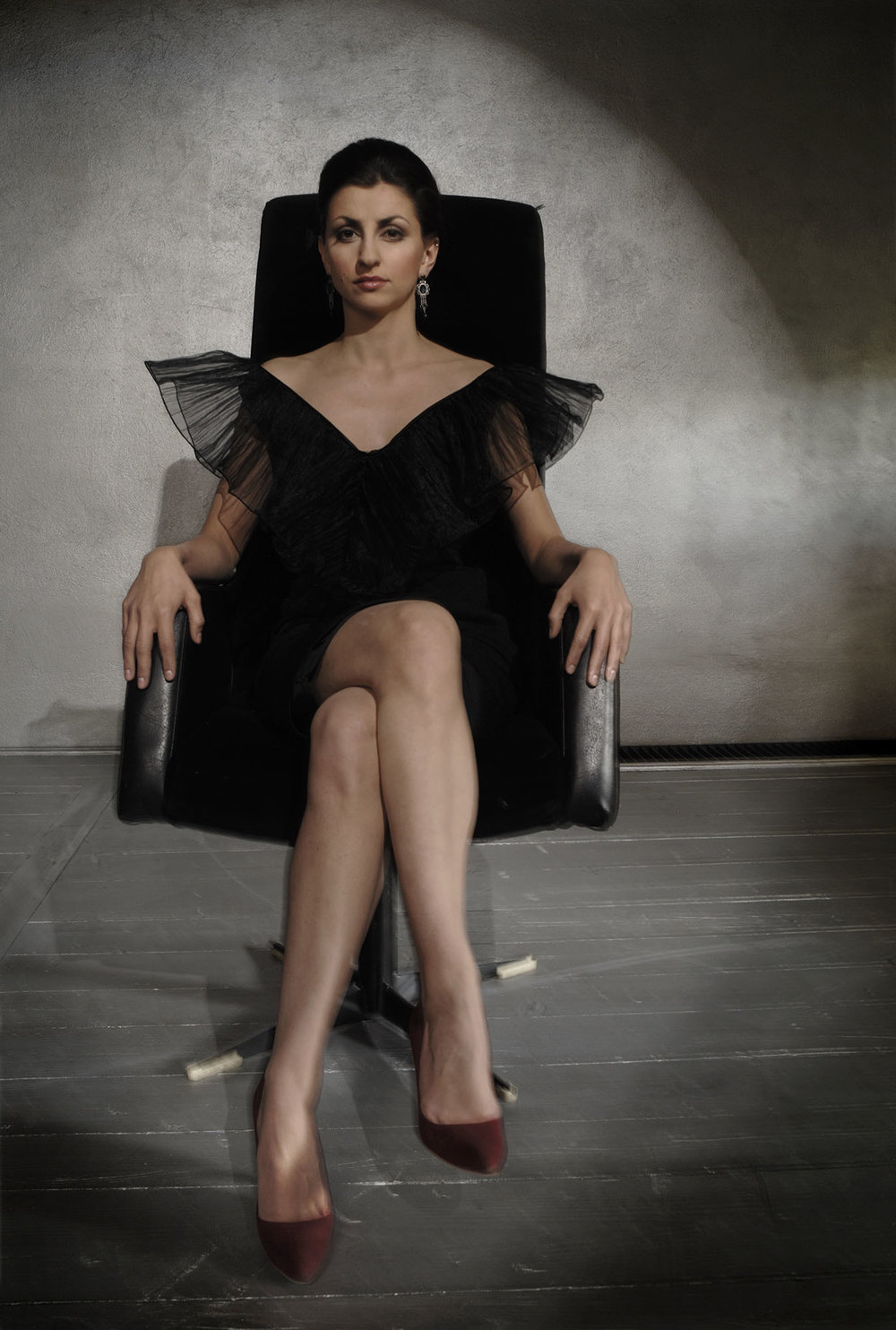 Dark haired lady sitting in a black chair