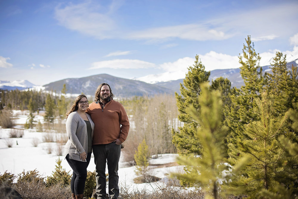 Engaged man and woman standing in meadow with mountains behind them in Frisco, Colorado