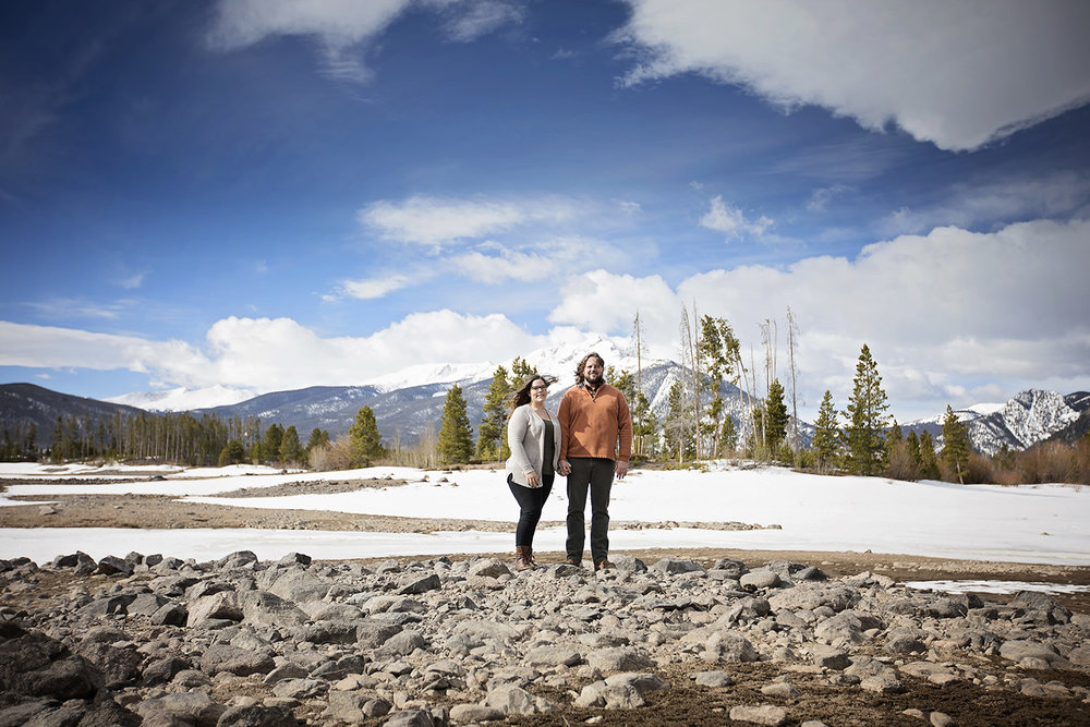 Wide angle of engaged couple standing in the shoreline of snowy Dillon Reservoir in Frisch, Colorado