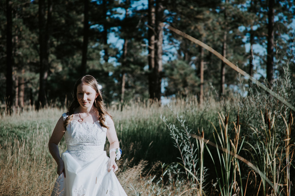 Bride in white wedding dress holding dress while walking through meadow