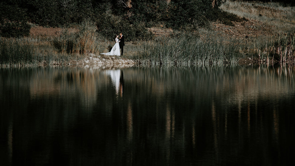 Bride and groom standing on shore of lake with reflection in water