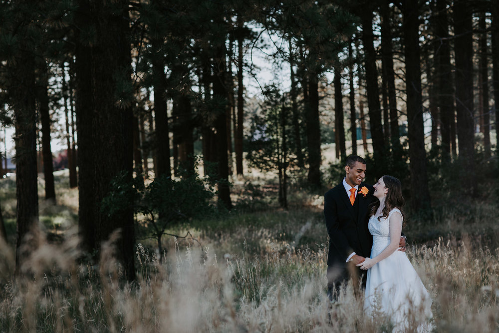 Wedding portrait of bride and groom with pine trees behind them