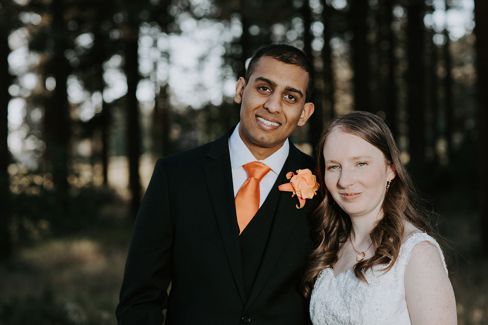 Bride and groom smiling in portrait with blurred background