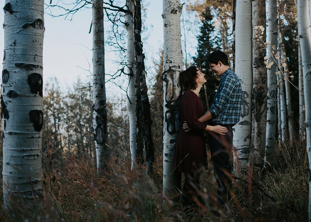 Couple facing each other smiling while leaning on white aspen trees