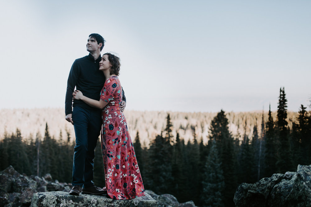 Engaged couple looking the same direction with an expansive view of pine trees and sky behind them