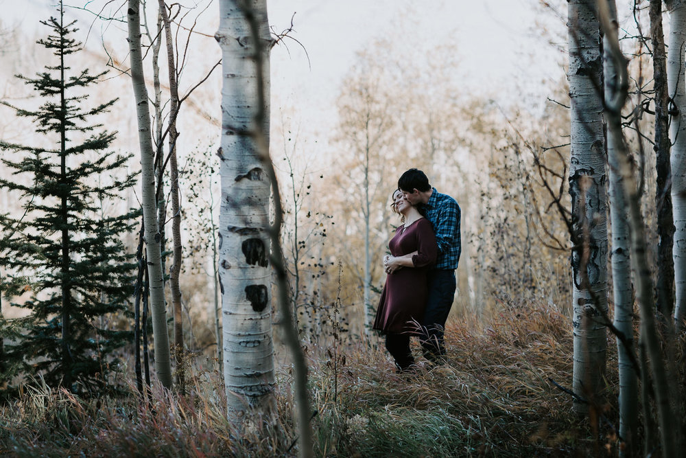 Man kissing his fiancé on the neck while standing in a field with aspen trees