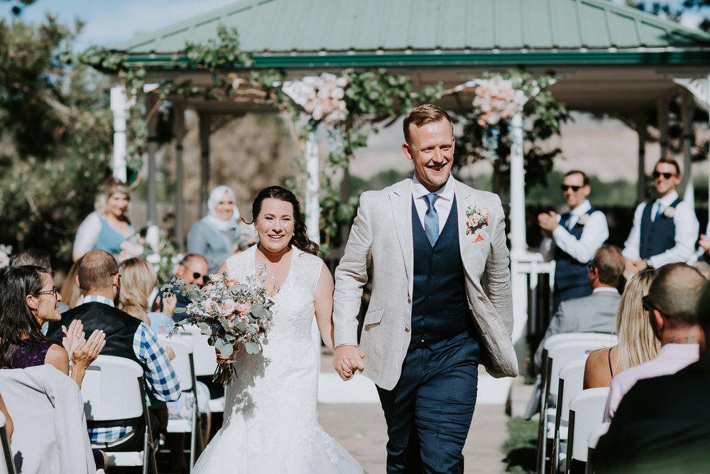 Happy smiling newlyweds walk down aisle after ceremony while guest clap
