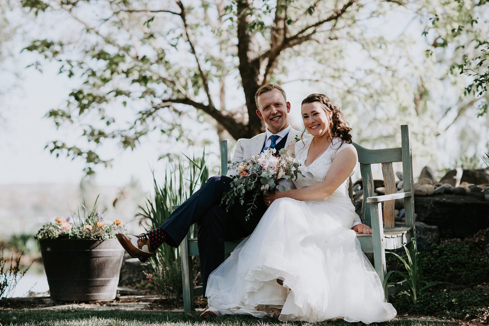 Bride and groom smiling while sitting on bench with trees blurred in background