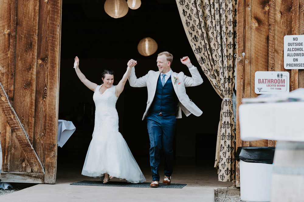 Celebrating newlyweds being announced into reception in front of barn