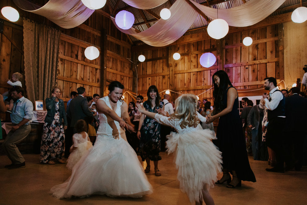 Candid moment of bride dancing with young niece and other guests