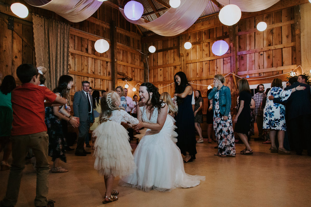 Bride laughing with young girl while dancing with paper lanterns adorning barn