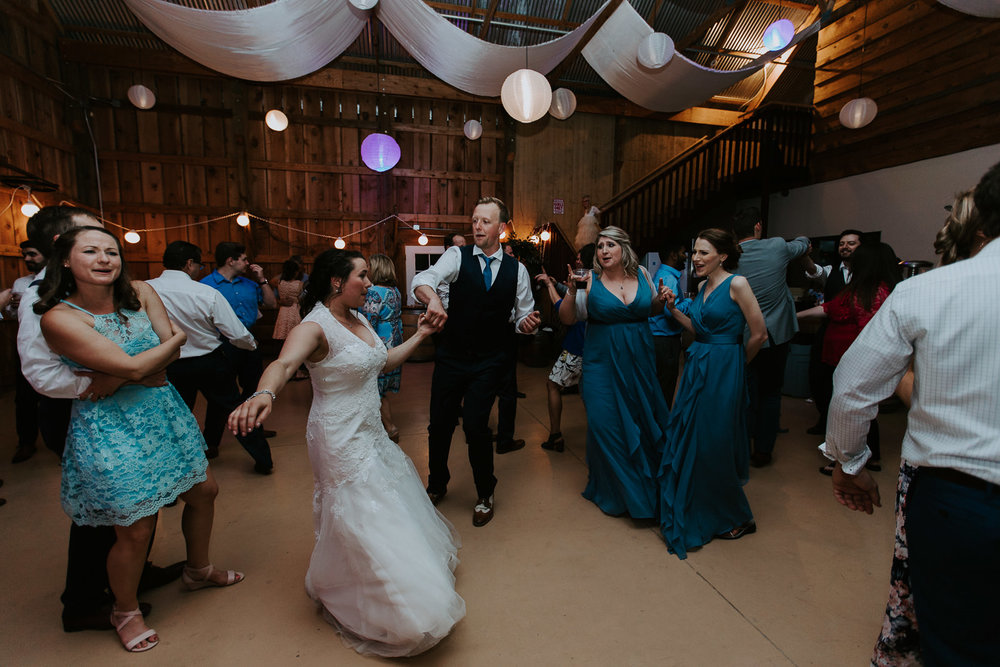 Bride and groom dancing with wide view of guests inside barn