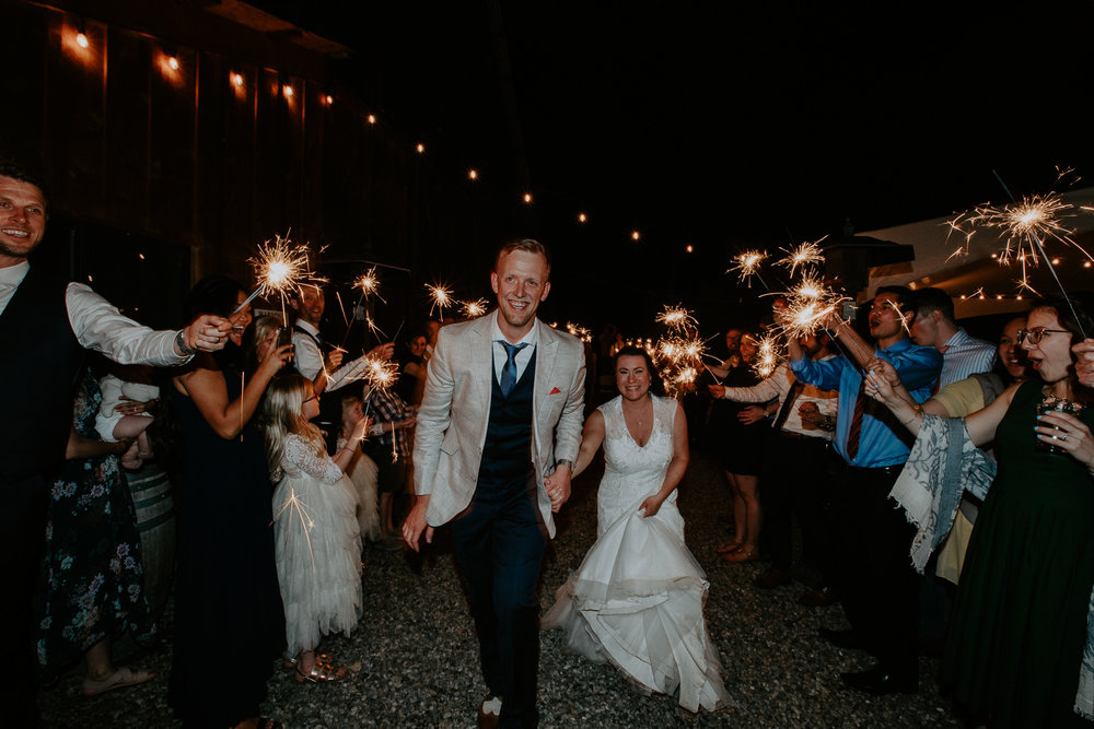 Bride and groom walking through sparklers held by guests
